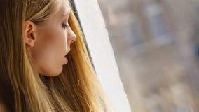 Entsetzte Jugendfrau, die durch schaut Stockfoto