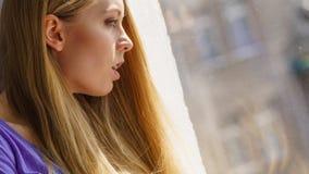 Entsetzte Jugendfrau, die durch schaut Lizenzfreies Stockbild