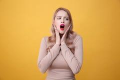 Entsetzte junge blonde Dame mit den hellen Make-uplippen Stockbild