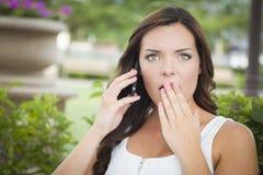 Entsetzte junge erwachsene Frau, die draußen am Handy spricht Lizenzfreie Stockfotos