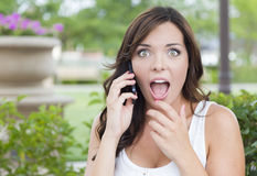 Entsetzte junge erwachsene Frau, die draußen am Handy spricht Lizenzfreies Stockfoto