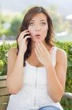 Entsetzte junge erwachsene Frau, die draußen am Handy spricht Lizenzfreies Stockbild