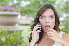 Entsetzte junge erwachsene Frau, die draußen am Handy spricht Stockbild