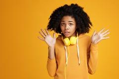 Entsetzte junge Frau des Afroamerikaners gekleidet in der zufälligen Kleidung und in den Kopfhörern über gelbem Hintergrund stockbilder