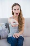Entsetzte junge Frau, die auf dem Sofa fernsieht sitzt Stockbild
