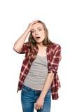 Entsetzte junge Frau, die Hand auf Stirn hält und Kamera betrachtet Lizenzfreie Stockbilder