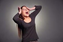 Entsetzte junge Frau, die oben schaut Stockfoto