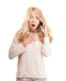 Entsetzte junge Frau, die am Telefon auf Weiß spricht. Stockfoto
