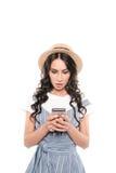 Entsetzte junge Frau im Strohhut unter Verwendung des Smartphone Lizenzfreies Stockfoto