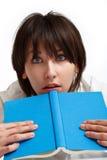 Entsetzte junge Frau mit einem Buch Lizenzfreies Stockfoto