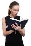Entsetzte junge Geschäftsfrau, die Tagebuch betrachtet lizenzfreie stockfotografie