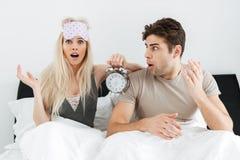 Entsetzte junge Liebhaber, die im Bett mit geöffnetem Mund sitzen und Wecker halten Lizenzfreies Stockbild