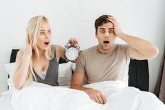 Entsetzte junge Paare, die im Bett mit geöffnetem Mund sitzen und Wecker halten Lizenzfreies Stockfoto