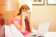 Entsetzte lustige zufällige junge Frau, die Laptop verwendet lizenzfreie stockfotos