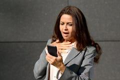 Entsetzte mittlere Greisin, die eine Textnachricht liest Lizenzfreie Stockfotos