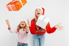 Entsetzte Mutter und Tochter, in Sankt-Hüten und in den Weihnachtsstrickjacken lizenzfreie stockfotos