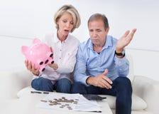 Entsetzte Paare, die piggybank halten Lizenzfreies Stockbild