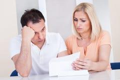 Entsetzte Paare, die Rechnung betrachten Lizenzfreies Stockbild