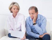 Entsetzte Paare, die Rechnung betrachten Stockbild