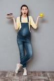 Entsetzte schwangere Dame, die süßen Kuchen und Apfel hält Lizenzfreies Stockbild