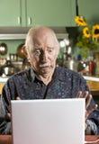 Entsetzter älterer Mann mit einer Laptop-Computer Lizenzfreies Stockbild