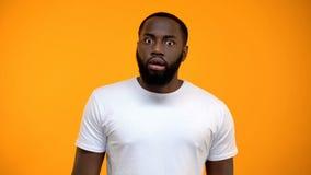 Entsetzter afro-amerikanischer Mann, der die Kamera lokalisiert auf gelbem Hintergrund betrachtet stockbilder