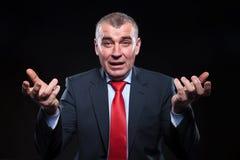 Entsetzter alter Geschäftsmann, der in Verwirrung gestikuliert Stockfotos