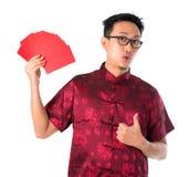 Entsetzter asiatischer chinesischer Mann, der viele roten Pakete anhält Stockbild