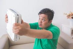 Entsetzter beleibter Mann beim Betrachten einer Gewichtsskala Stockfotografie