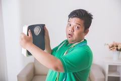 Entsetzter beleibter Mann beim Betrachten einer Gewichtsskala Lizenzfreies Stockbild