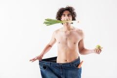 Entsetzter dünner Kerl, der nur Obst und Gemüse isst Stockbild