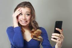 Entsetzter Frauenblick auf Telefon Stockfoto