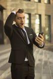 Entsetzter Geschäftsmann, der Handy betrachtet Stockfotos