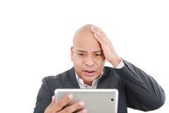 Entsetzter junger Geschäftsmann mit einer Tablette lizenzfreie stockfotografie