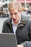 Entsetzter junger Mann mit Laptop Stockfotografie
