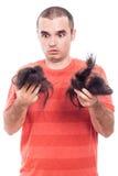 Entsetzter kahler Mann, der sein rasiertes Haar hält Lizenzfreie Stockfotos