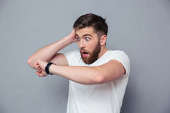 Entsetzter Mann, der auf Armbanduhr schaut Stockbild