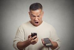 Entsetzter Mann, der auf dem Smartphonetaschenrechner angewidert mit Finanzwechseln schaut stockbild