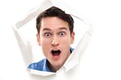 Entsetzter Mann, der durch Papierloch schaut Stockbild