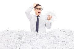 Entsetzter Mann, der einen Stapel des zerrissenen Papiers betrachtet Lizenzfreies Stockfoto