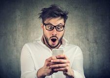 Entsetzter Mann, der gute Nachrichten am Telefon hat stockfoto