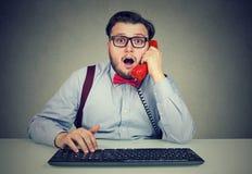 Entsetzter Mann, der am Telefon am Arbeitsplatz spricht stockbild