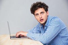 Entsetzter Mann, der am Tisch mit Laptop sitzt Lizenzfreie Stockfotografie