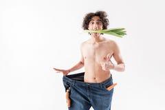 Entsetzter schlanker Kerl, der gesunde Ernährung genießt Stockfoto