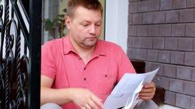 Entsetzter und gestörter junger Mann, der Papier, Rechnungen betrachtet stock video footage