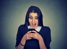 Entsetztes aufpassendes Mobiltelefon der jungen Frau stockfoto