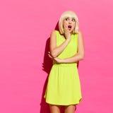 Entsetztes blondes Mädchen auf der rosa Wand Stockfotografie
