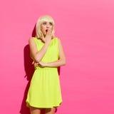 Entsetztes blondes Mädchen auf der rosa Wand Stockfoto