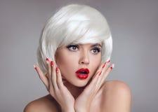 Entsetztes Gesicht Blonde Frau mit den roten Lippen und Maniküre nagelt surpr Stockbilder