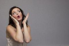 Entsetztes hübsches Mädchen mit dem offenen Mund, der weg schaut Stockfoto